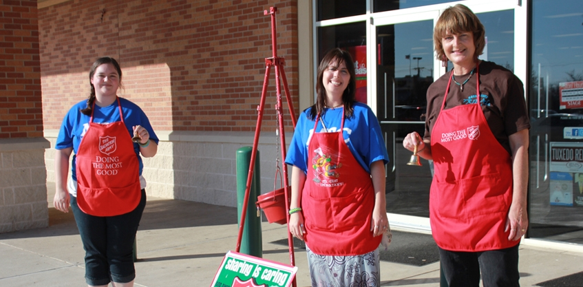 Students outside store with Salvation Army aprons and bells